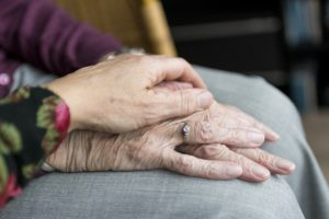 A caregiver comforts a terminally ill person