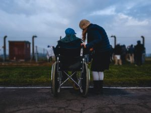 person in a wheelchair with a family member