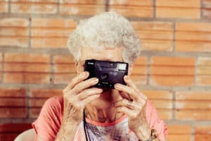 One of the fun activities for seniors is taking photos- like this older woman taking a photo with a disposable camera