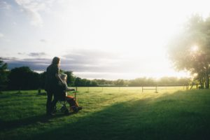 a family caregiver pushes a loved one in her wheelchair outside in the grass toward a sunset