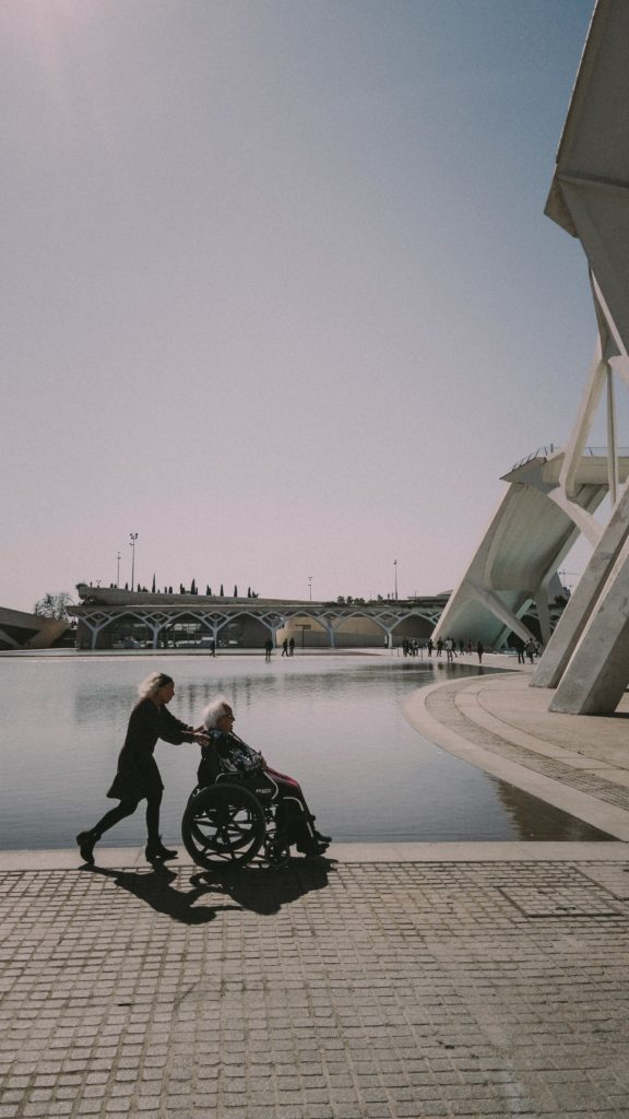 A couple with a woman pushing a man in a lightweight wheelchair along the water near a geometric building