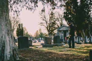 A senior man overlooks a grave.