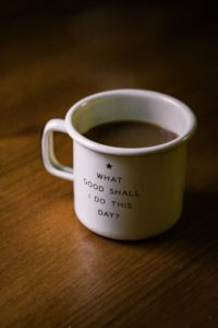"a cup of coffee with the inspirational quote for caregivers ""What good shall I do this day?"""