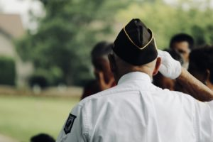 A senior veteran salutes others.