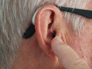 Discreet hearing aid in an old man's ear