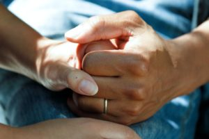 caregiver holds hands with a loved one
