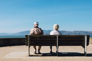 An elderly couple sits on a bench