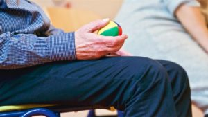 An elderly man holds a therapy ball