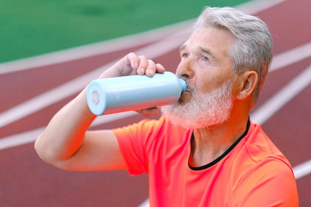 An elderly man stays hydrated