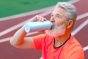 An elderly man stays hydrated