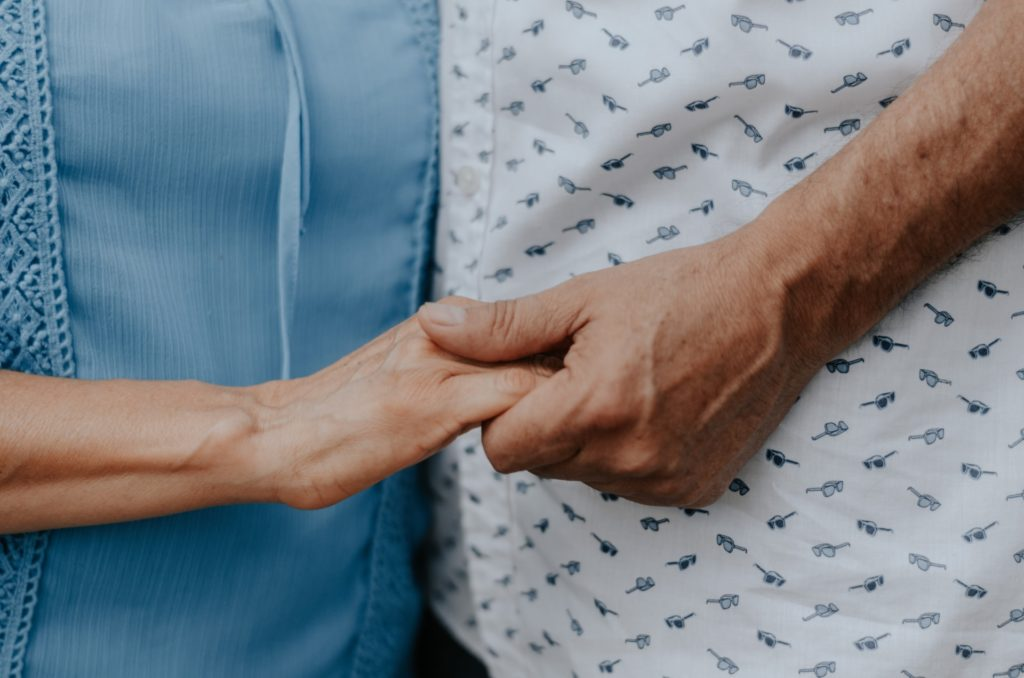 A patient and family member hold hands