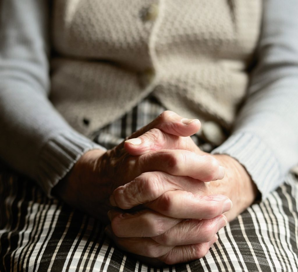 A senior woman clasps her hands