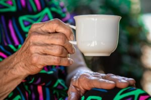 A senior woman drinks a cup of tea