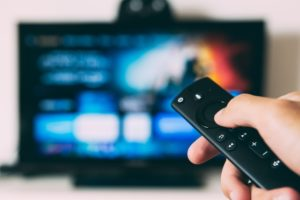 Someone holds a fire stick TV remote up to a TV
