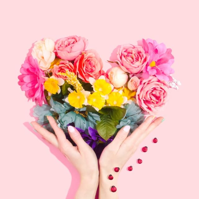Two hands hold flowers, a lovely gift for an older woman