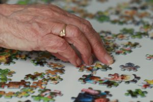 A senior enjoys a jigsaw puzzle