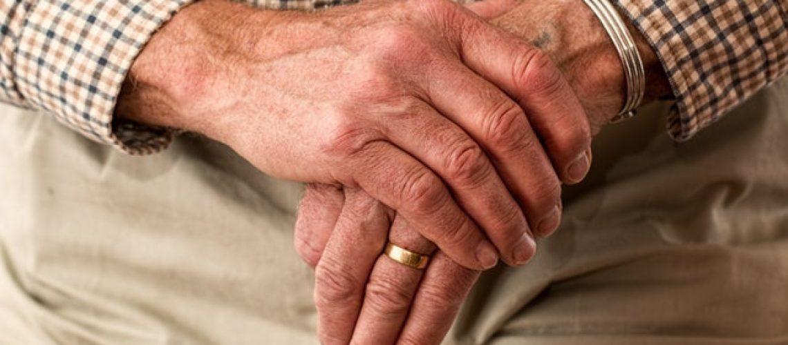 Elderly man with crossed hands