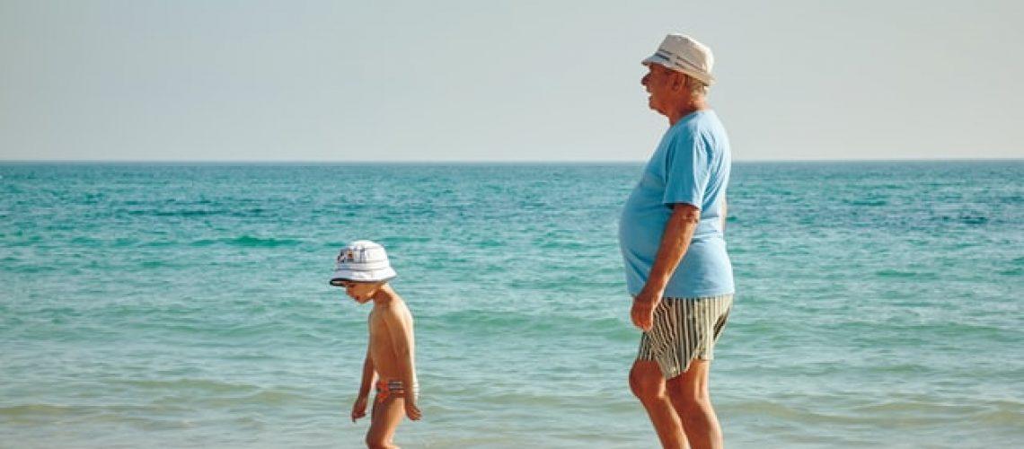 grandchild and grandparent on beach