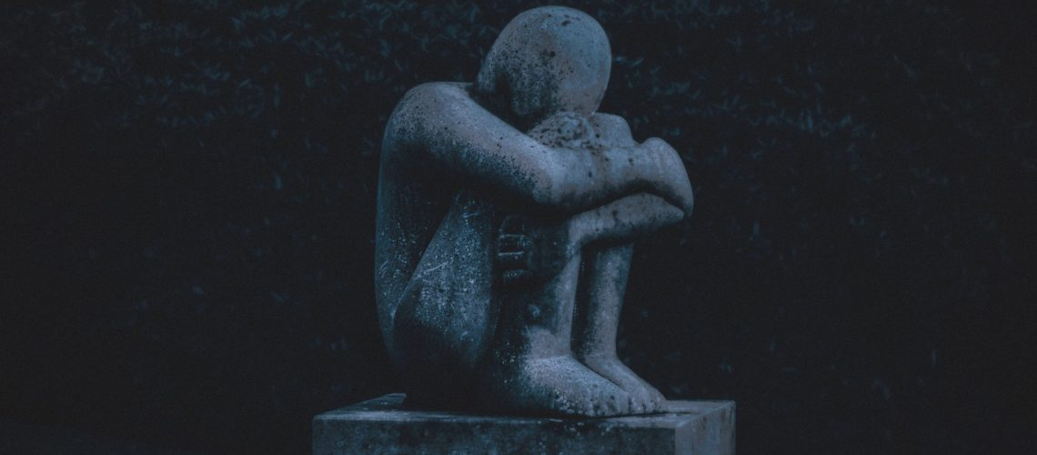 Statue of a person grieving
