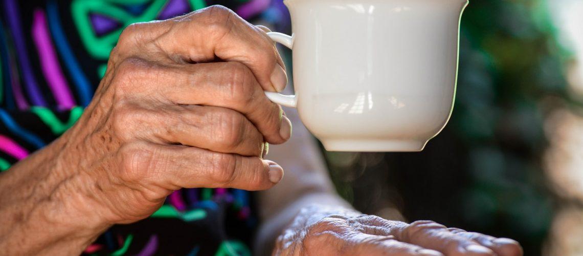 A senior woman drinks a cup of tea
