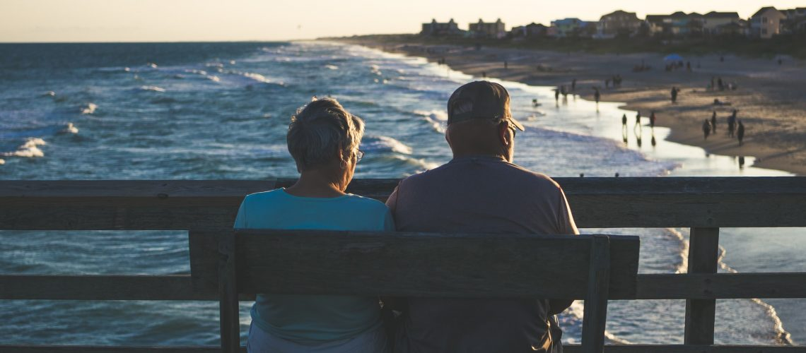 A senior couple sits on a bench