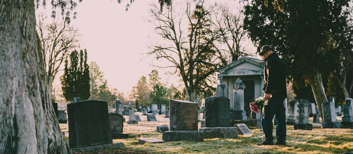 A senior man overlooks a grave.