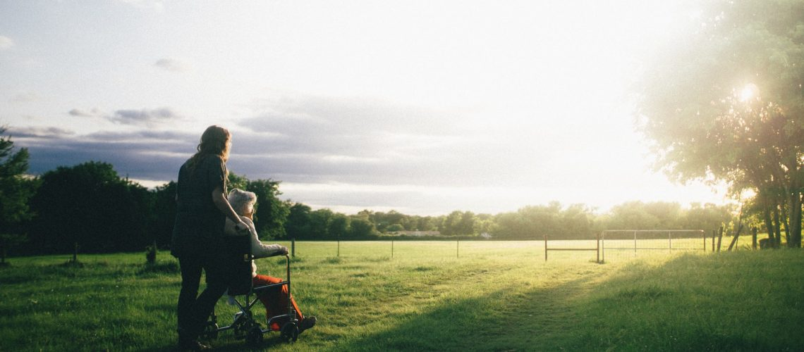 A caregiver strolls outside with a hospice patient