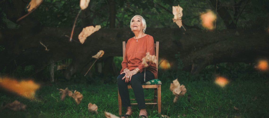 An elderly woman sits outside