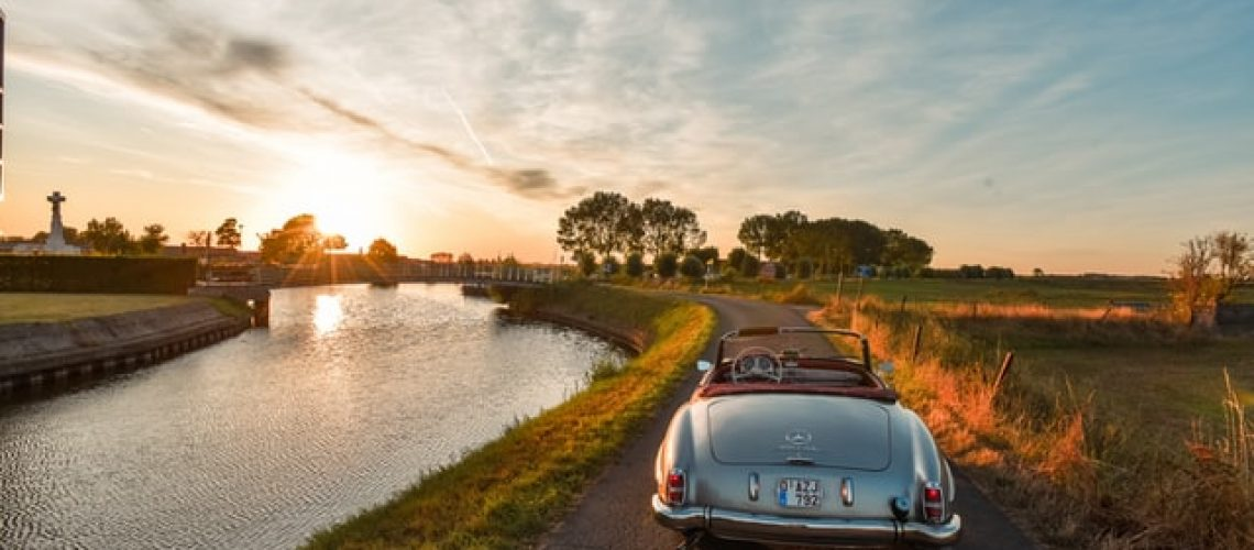 A vintage car riding next to a lake at sunset.