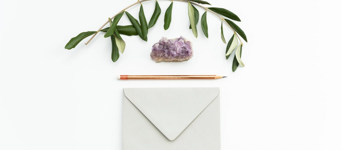 A celebration of life invitation with a plant, a stone, and a pencil