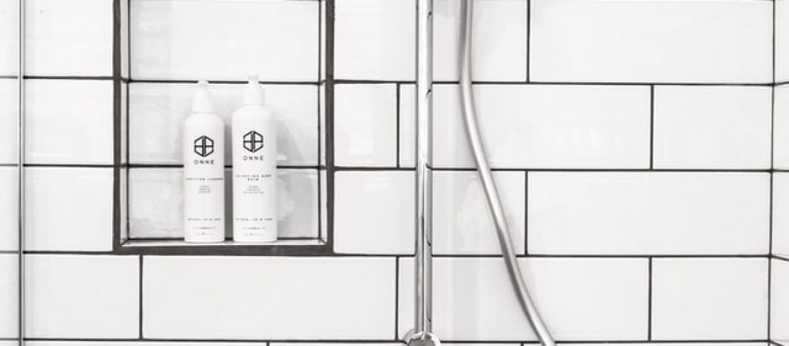 A shower head next to shampoo and conditioner