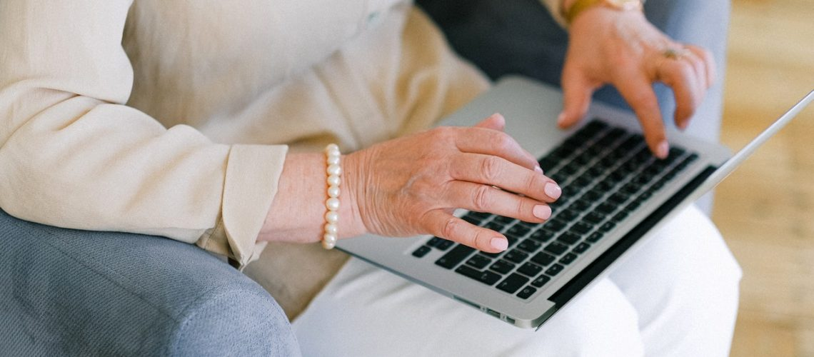 An elderly woman types on her computer