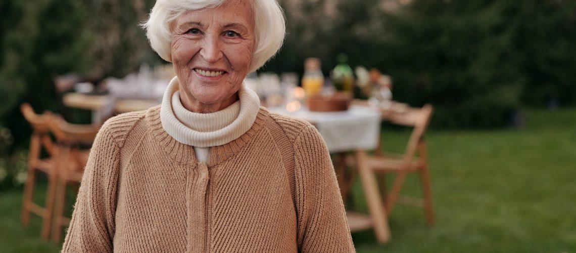 An elderly woman stands in her backyard