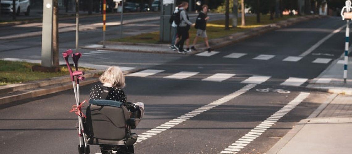 A woman ride a mobility scooter down the bike lane.