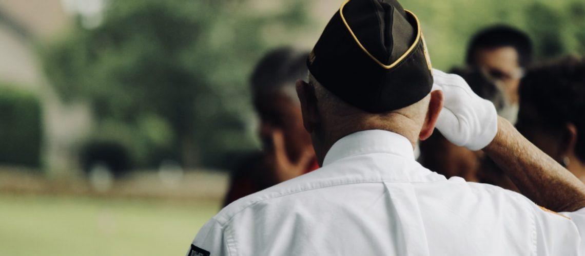 A senior veteran salutes others.