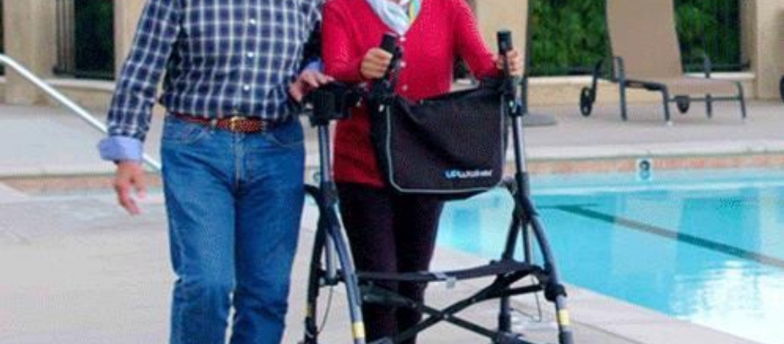 A man walks next to a woman as she uses her upright walker