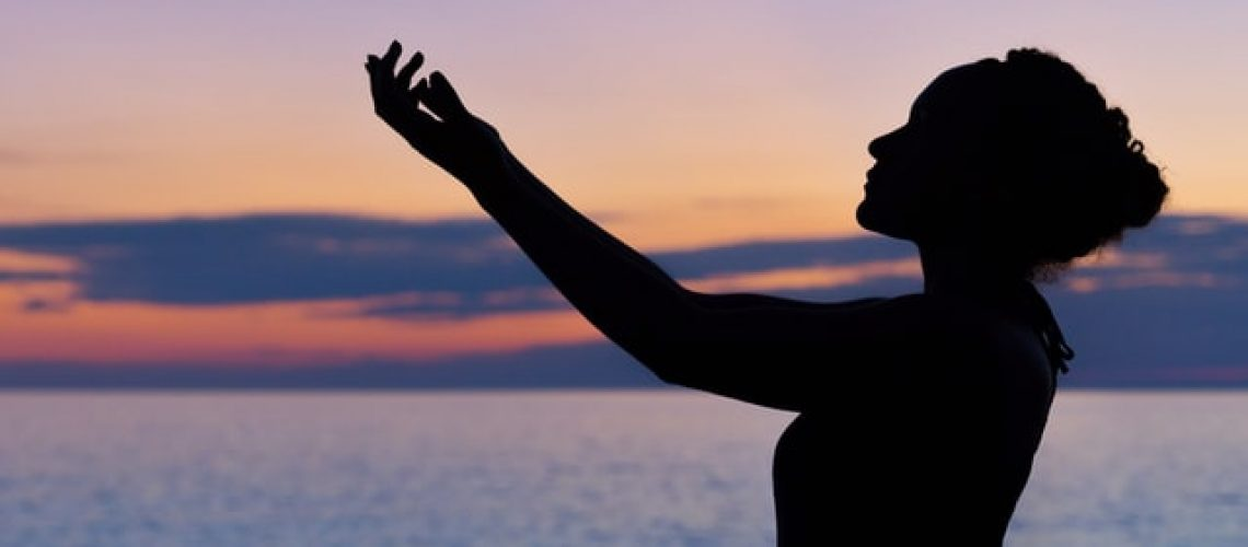 a silhouette of a woman in prayer by a lake
